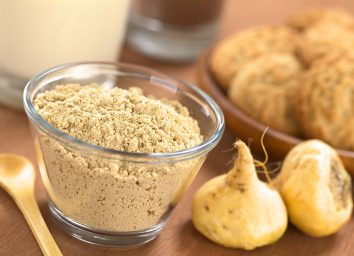 maca root and powder with wooden spoon