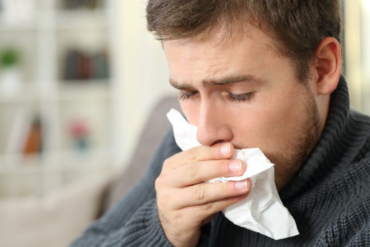 Man coughing covering mouth with a tissue