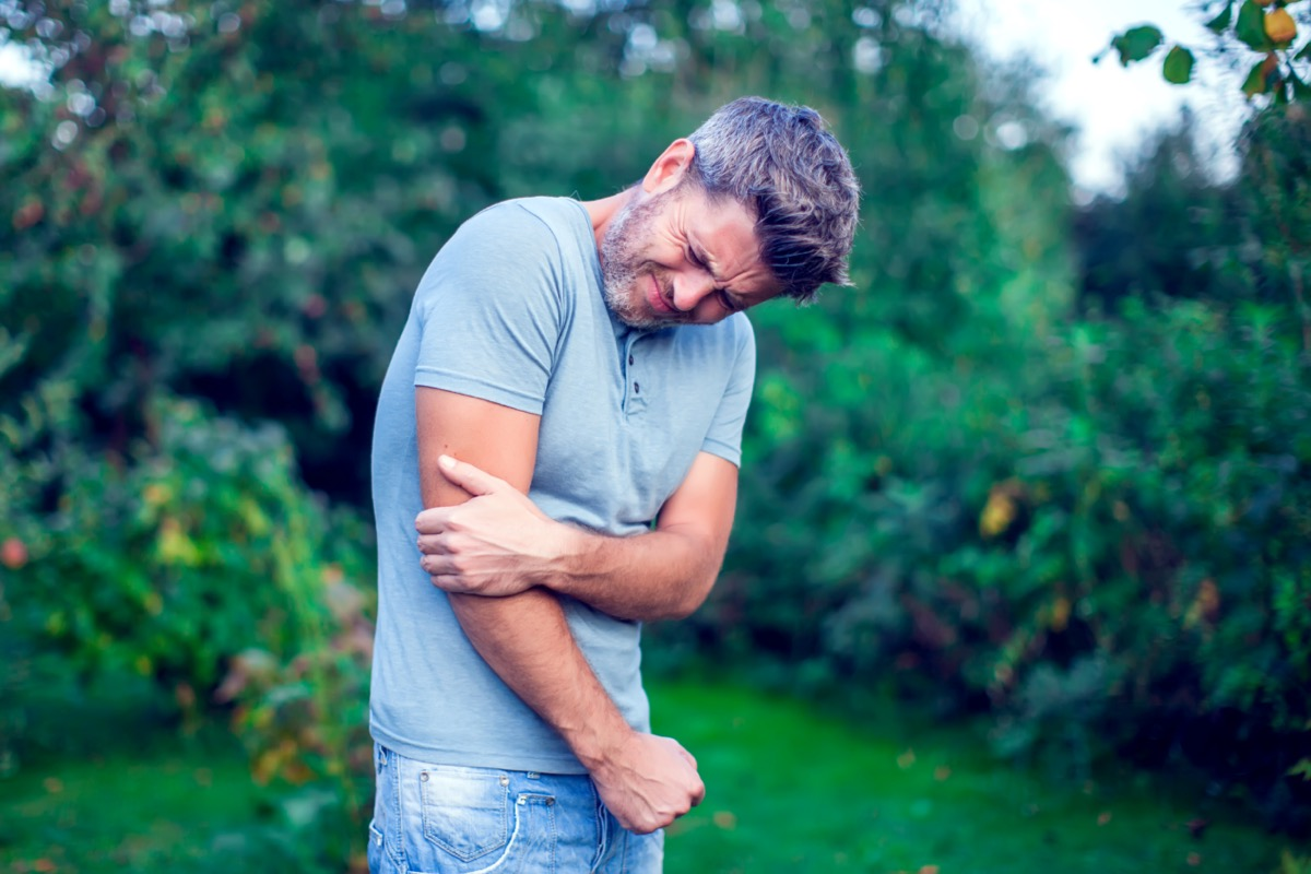 man with dark hair suffering from elbow pain outdoor