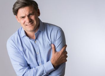 Mature Man Clutching Arm As Warning Of Heart Attack