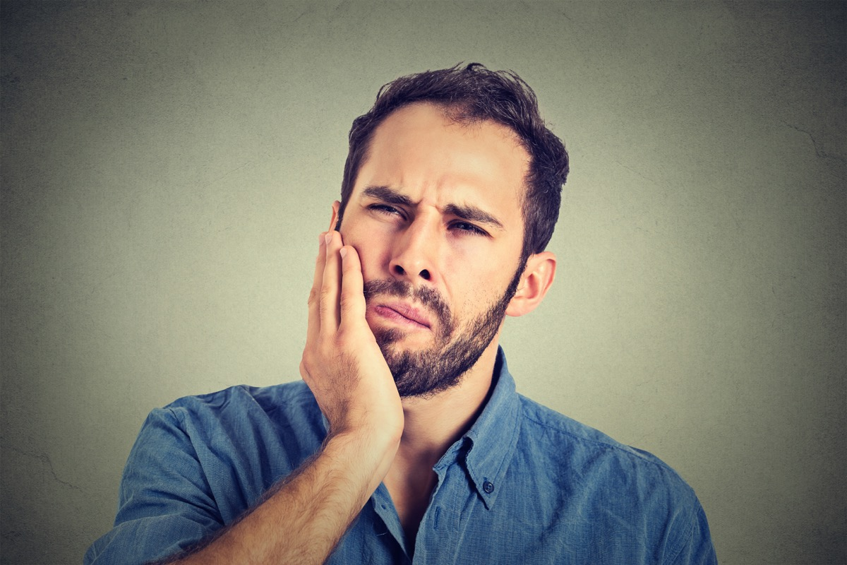 young man with a toothache tooth pain