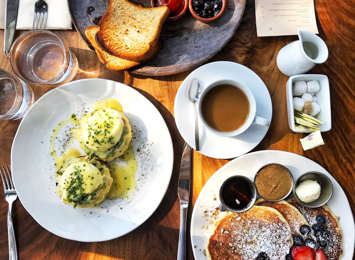 a breakfast spread from above with pancakes, eggs benedict, coffee, and toast from martina