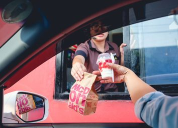 McDonald's employee handing customer food through the drive thru window