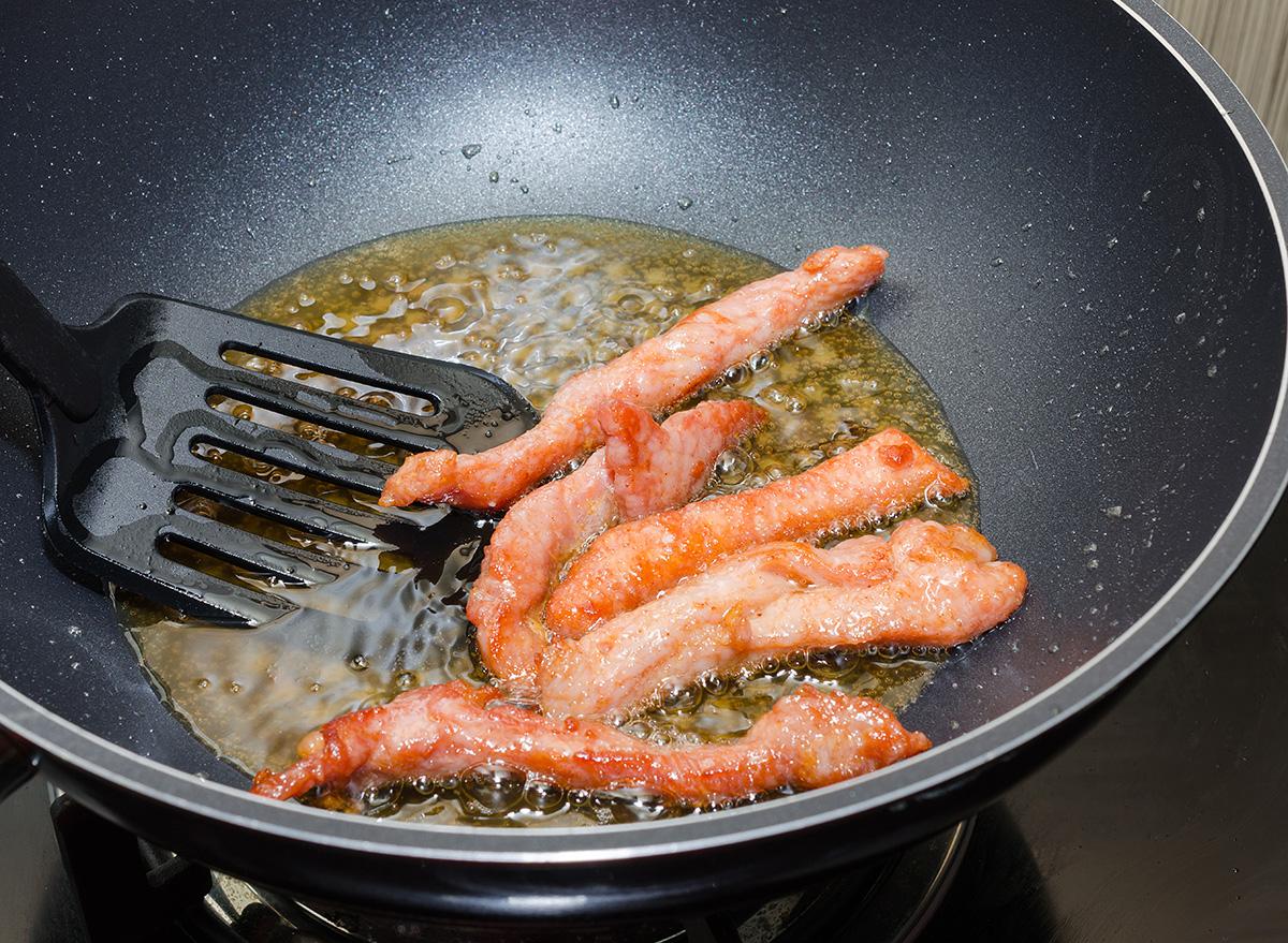 meat strips fried in a black pan