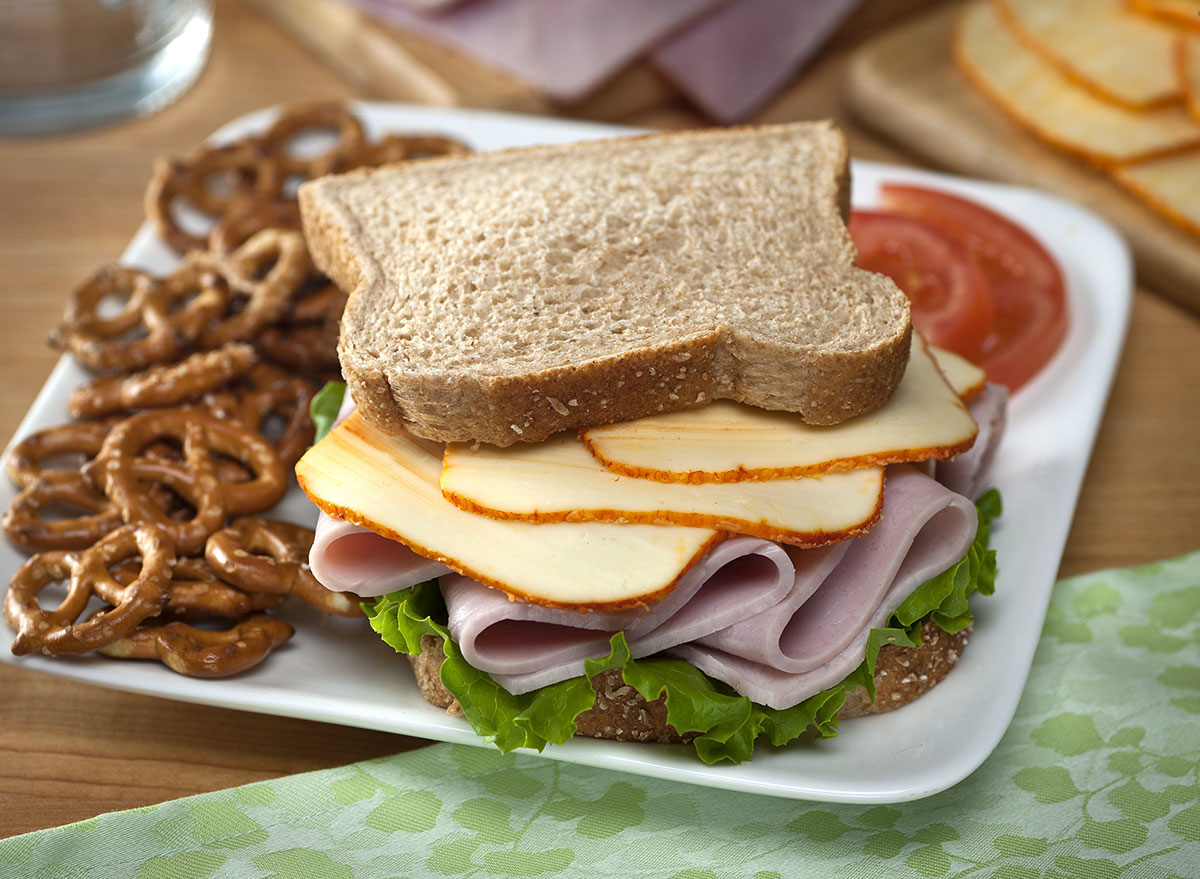 Muenster cheese and ham sandwich with side of pretzels on a plate