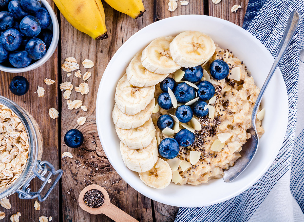 oatmeal with banana and blueberries in a white bowl on wood