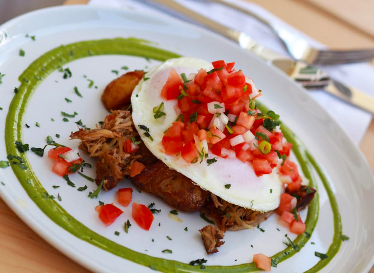pulled pork underneath an egg with pico de gallo on top surrounded by chimichurri sauce on a white plate from over easy