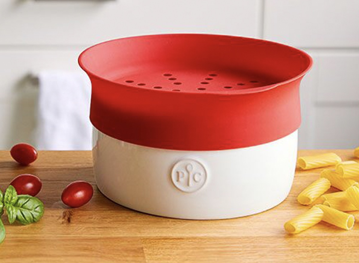 red and white microwave pasta cooker next to cherry tomato on butcher block counter