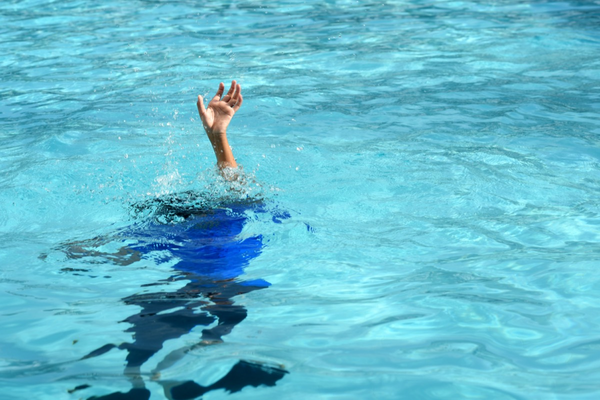 Male boy struggling underwater drowning in swimming pool.