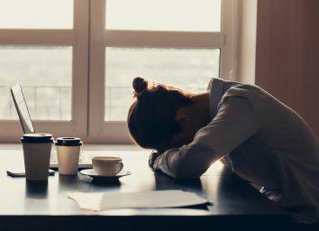 woman lying her head down on a desk