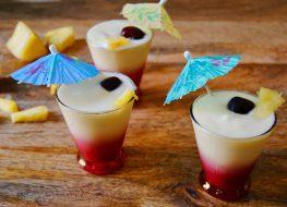 paleo pina colada smoothie in three glasses with little umbrellas