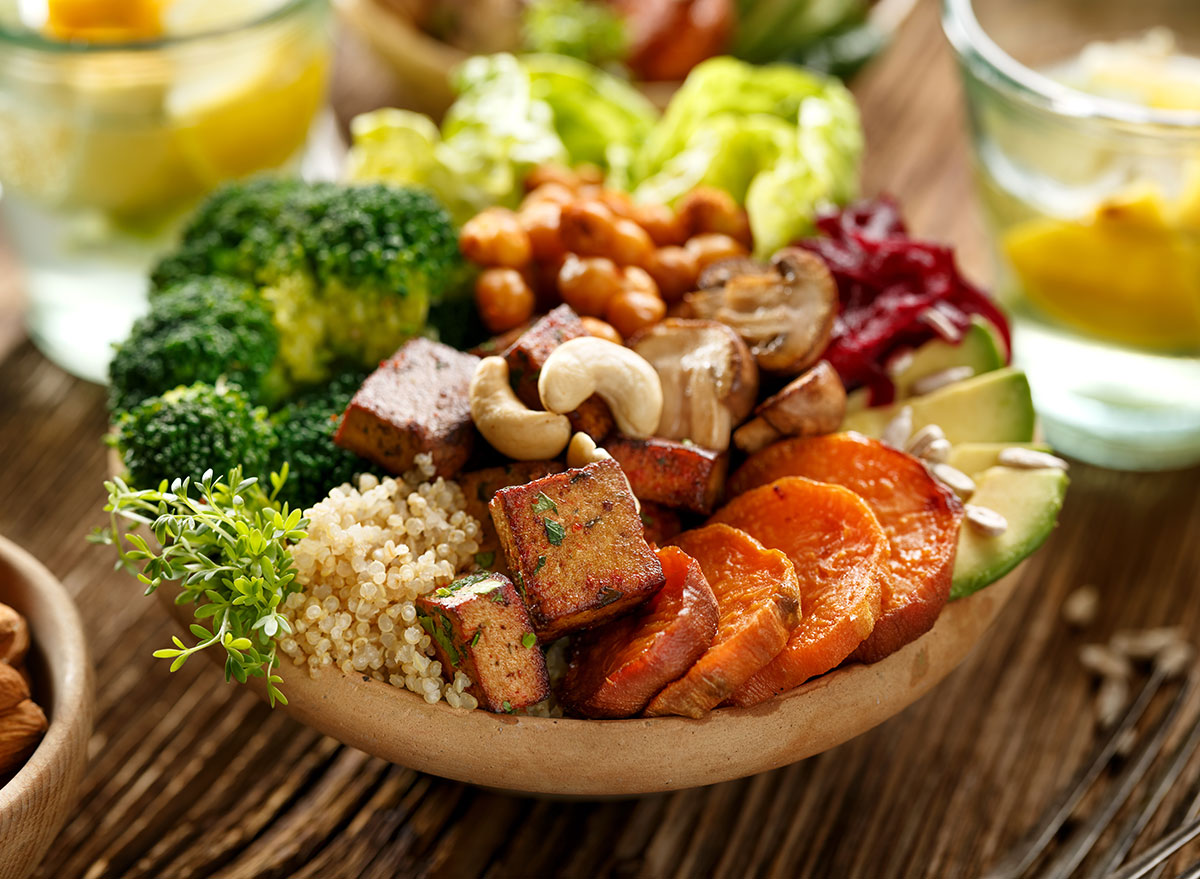 Buddha bowl of plant based foods including broccoli, nuts, tofu, carrots, avocado, and much more