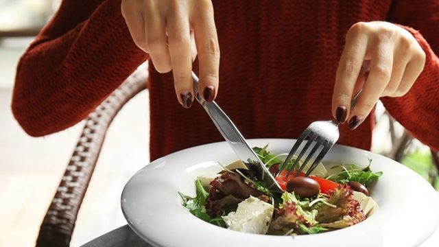 Woman eating a salad with vegetables and tofu.