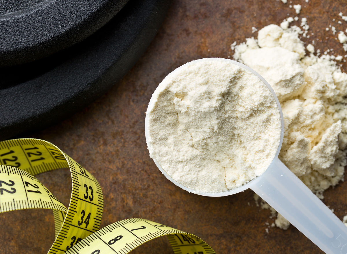 Scoop of protein powder with weight loss measuring tape