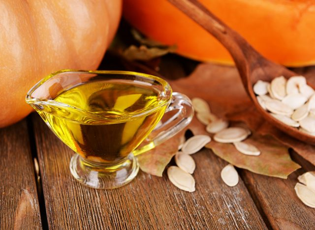 pumpkin seed oil in glass serving container on wooden background