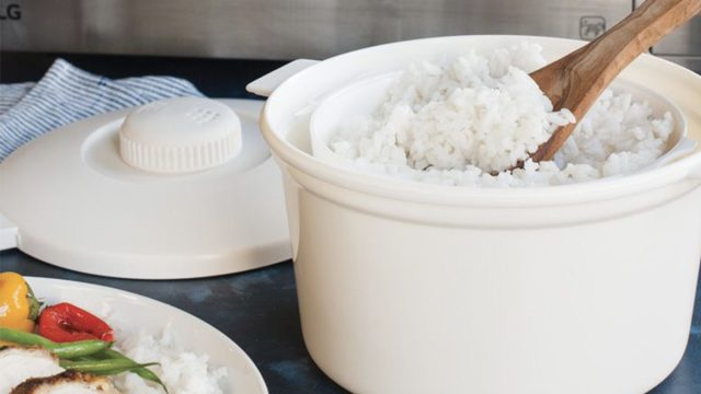 white rice cooker with wooden spoon in it