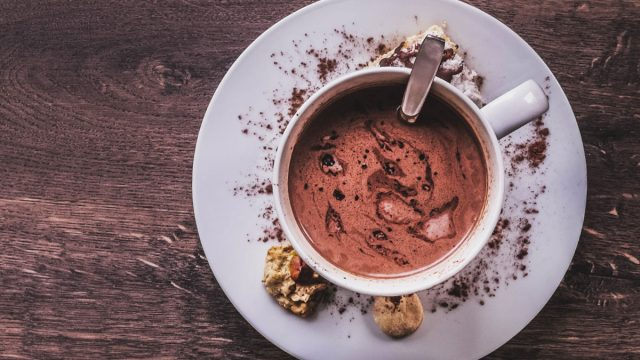 rich hot cocoa powder in mug on white plate