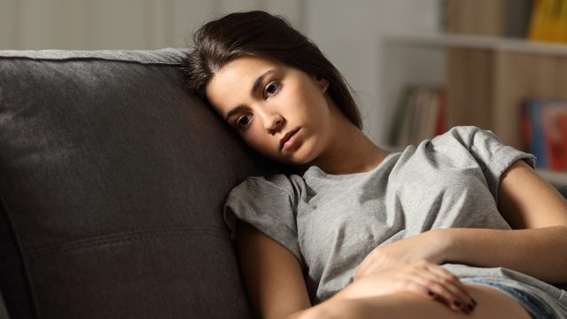 sad woman sitting on a couch