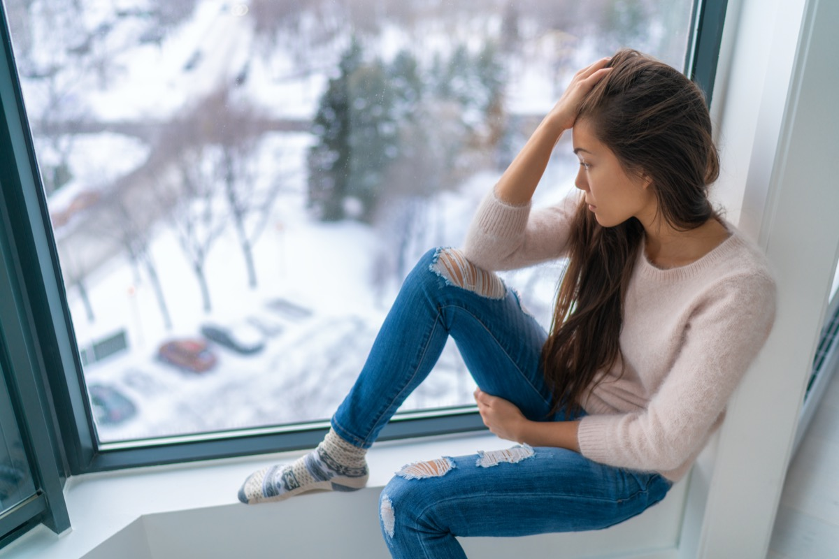 Winter depressed sad girl lonely by home window looking at cold weather upset unhappy