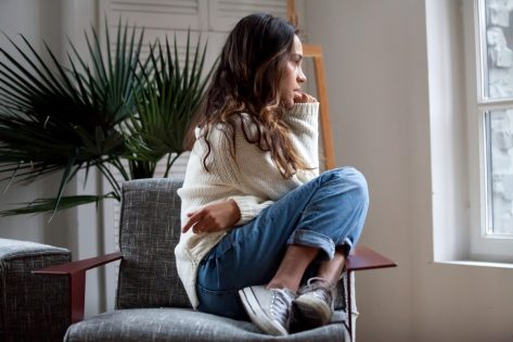 Sad thoughtful teen girl sits on chair feels depressed