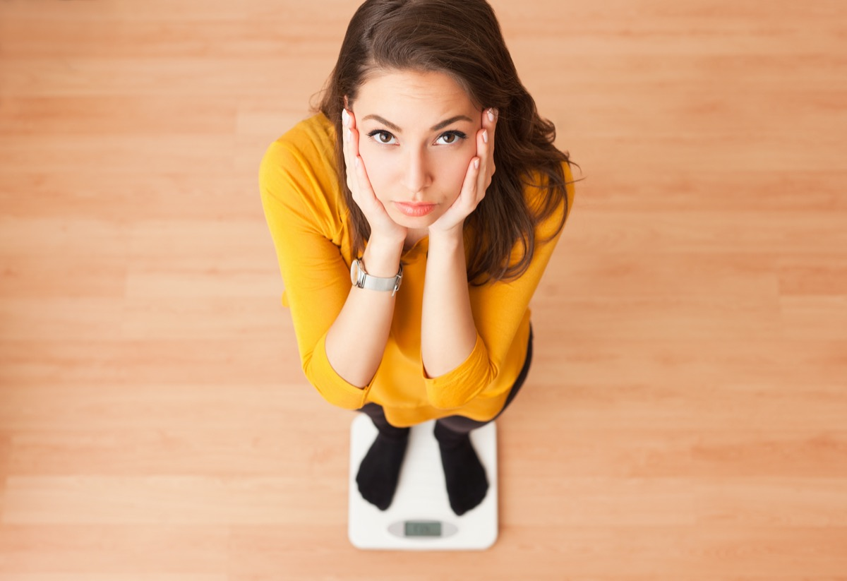 young brunette woman standing on a scale