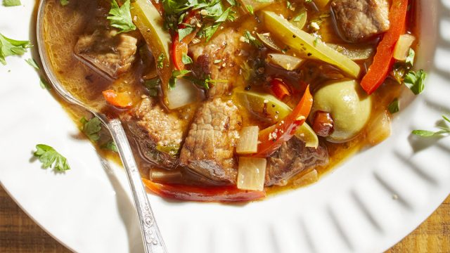 spanish pepper beef stew with olives in a white bowl