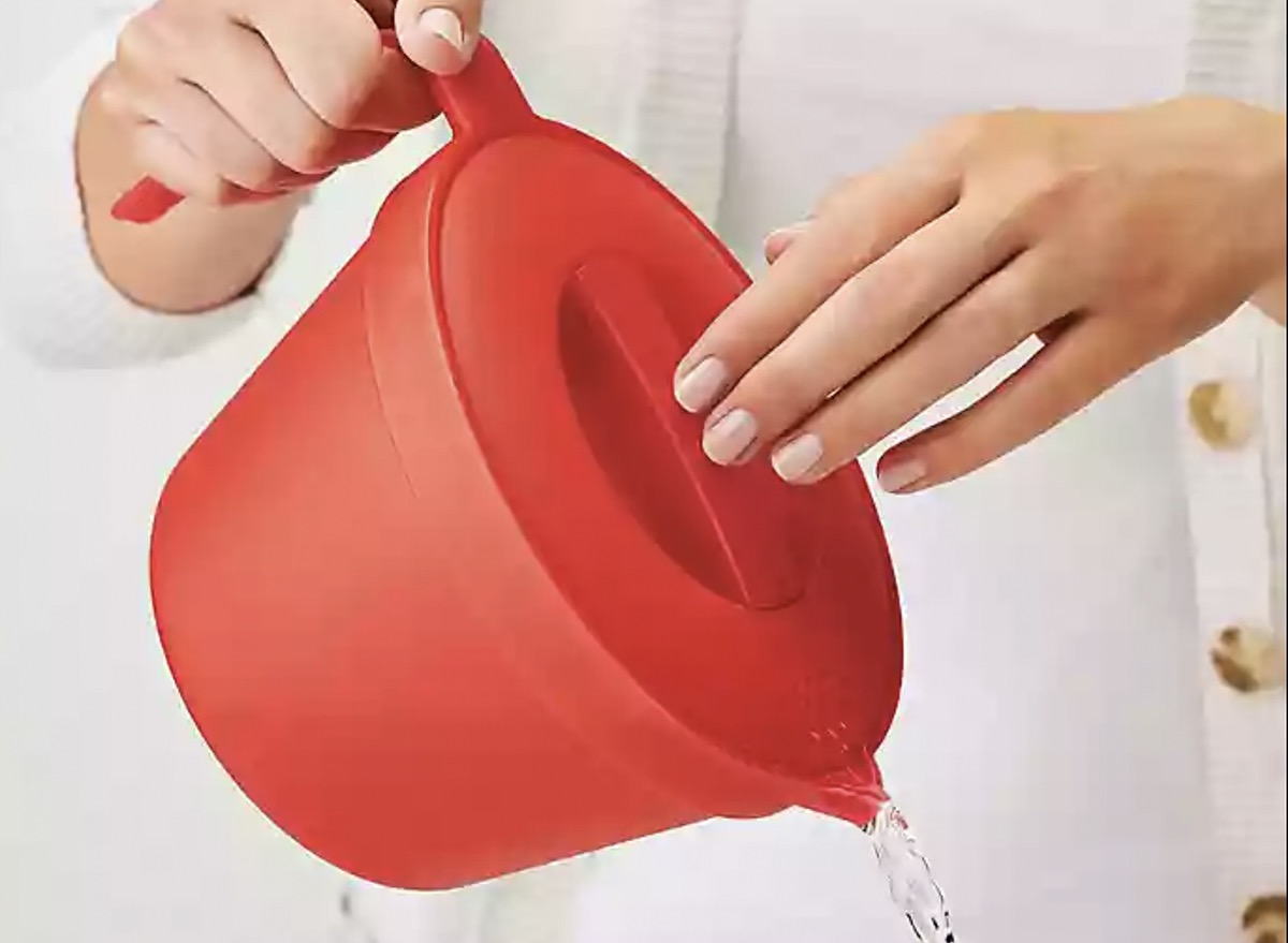woman's hand pouring water from red kettle