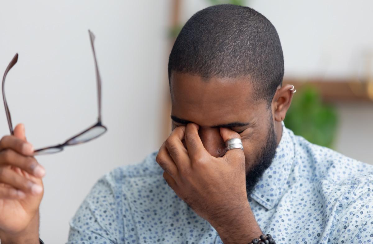 businessman taking off glasses rubbing dry irritated eyes