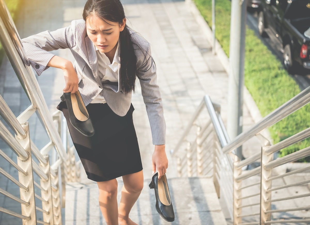 Women walk up the ladder with bare feet and Holding black high heels with fatigue