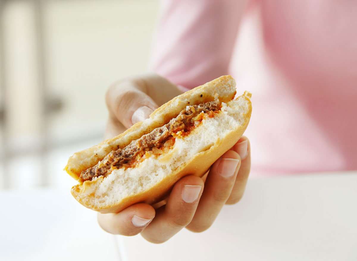 Holding a hamburger upside down with a bite in it