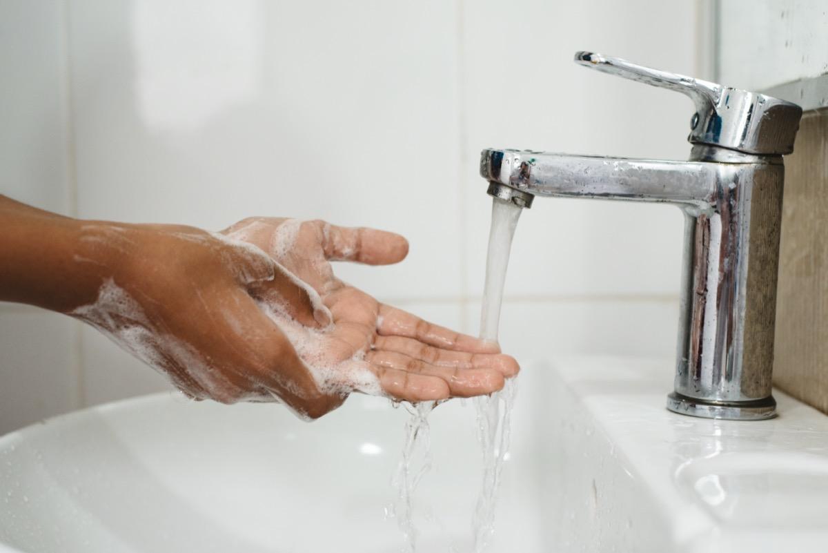 scrubbing soapy hand against washbasin