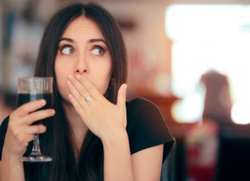 Woman covering her mouth after drinking cola