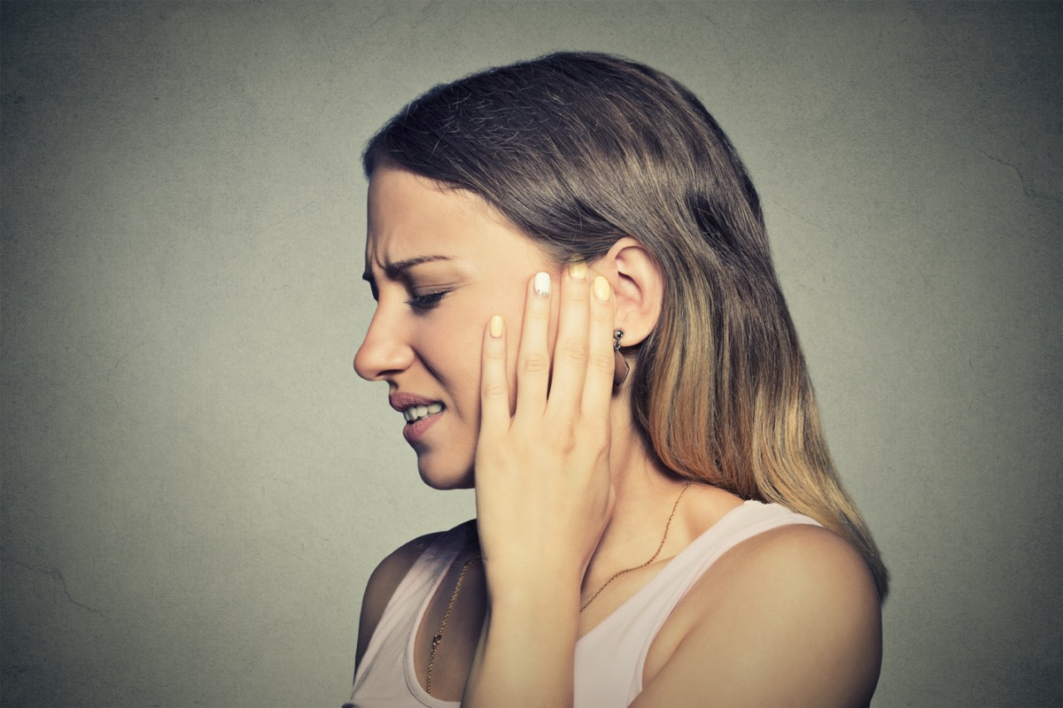 woman having ear pain touching her painful head