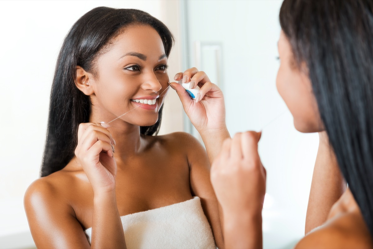 woman cleaning her teeth with dental floss and smiling while standing against a mirror in bathroom