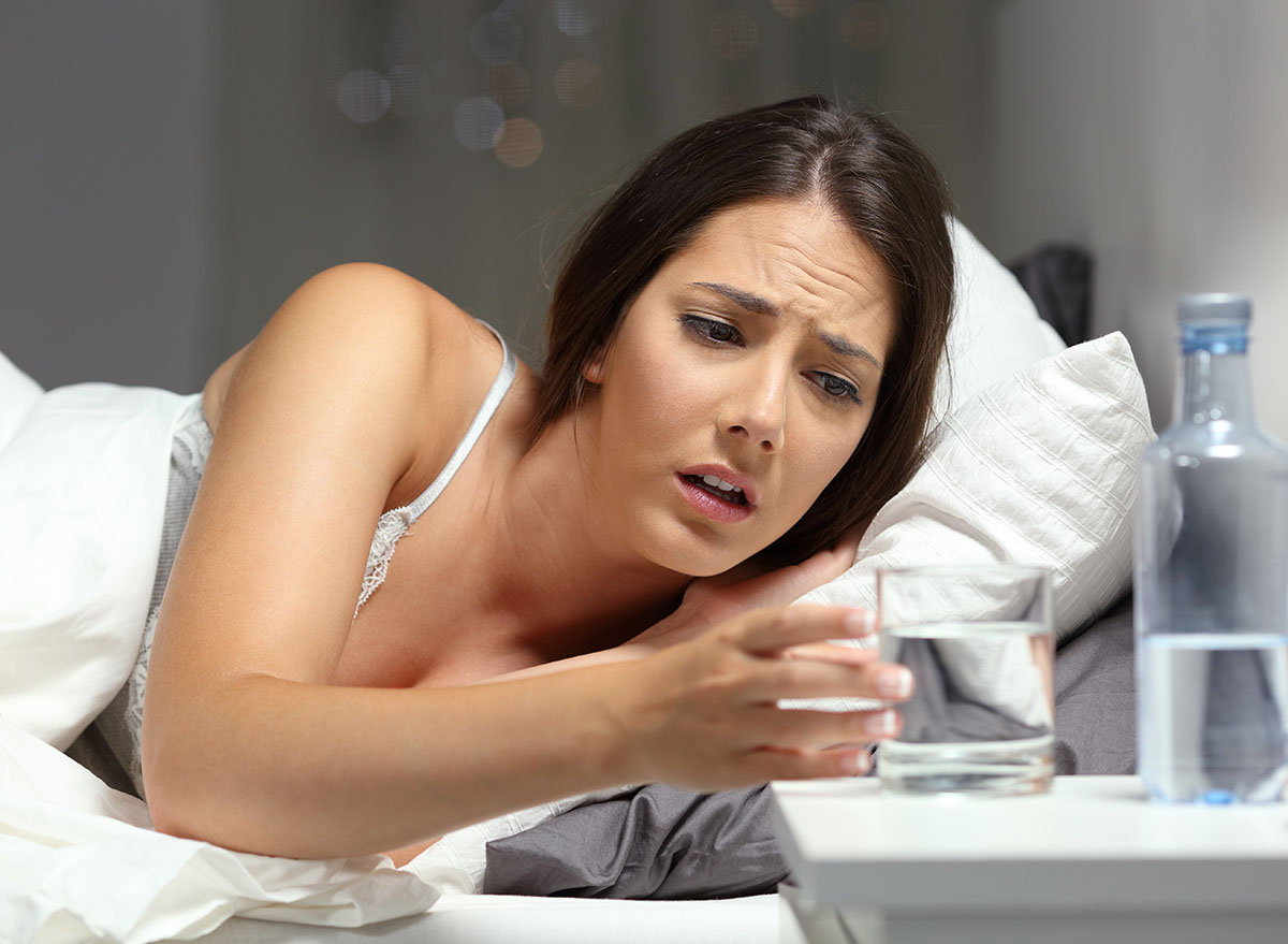 woman in bed feeling thirsty reaching for water