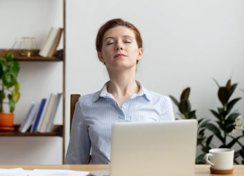 Businesswoman breathing, stretching shoulders after hard work feeling discomfort at office desk work