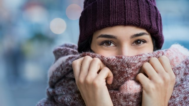 woman covering face with woolen