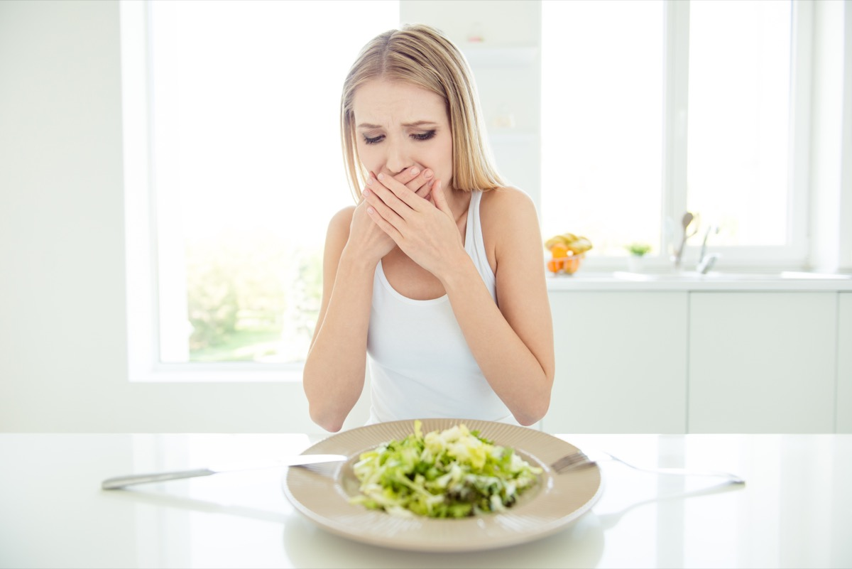 frustrated confused tired scared displeased lady covering mouth with palms do not want to eat salad sitting at table looking at bowl