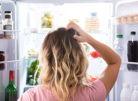 woman standing at fridge hungry and confused