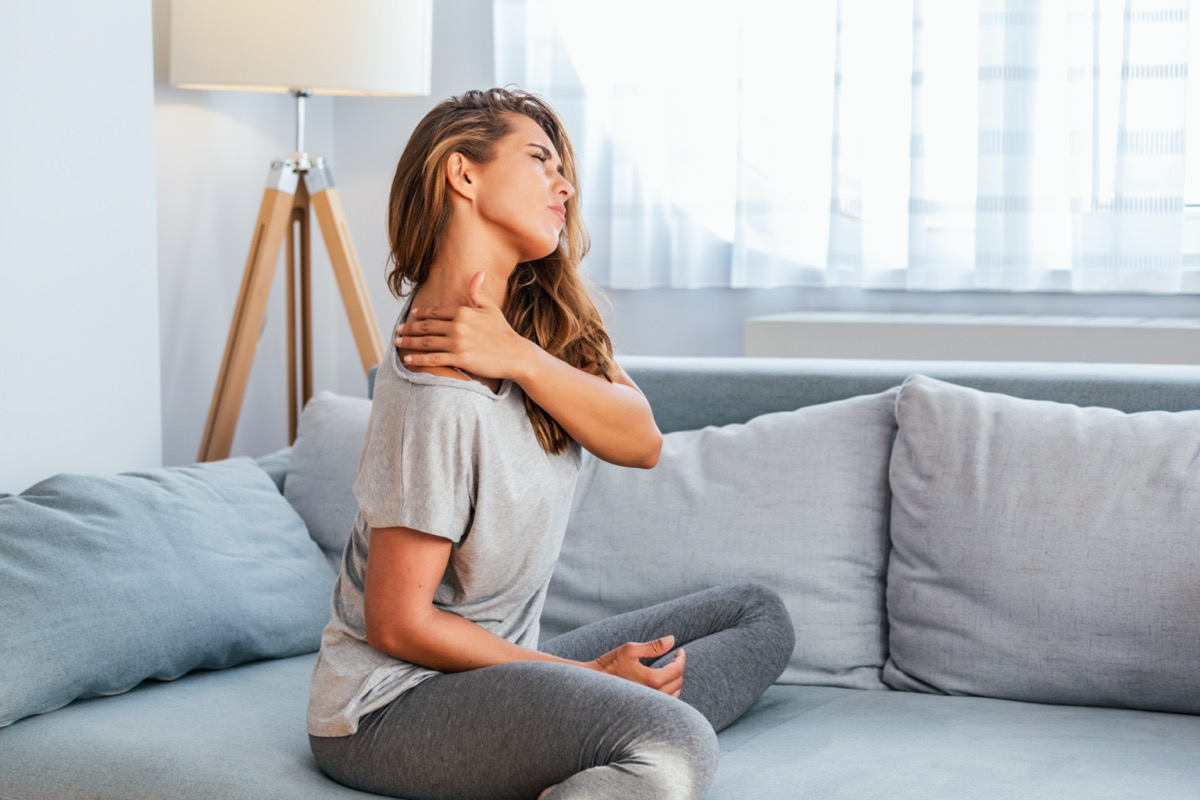 woman sitting on the bed and holding painful shoulder with another hand