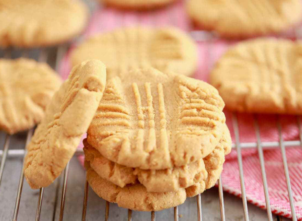 Peanut butter cookies stacked up on a cooling rack with a pink napkin