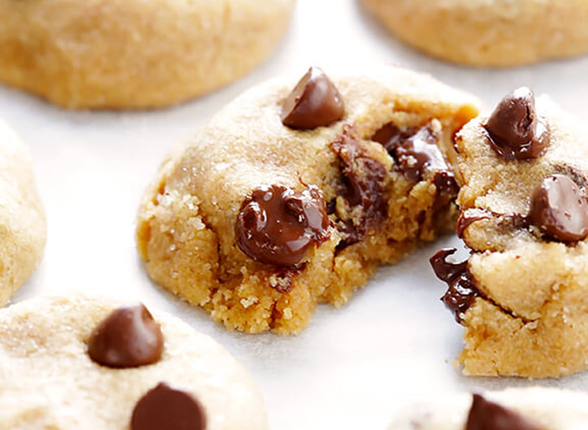Splitting a peanut butter chocolate chip cookie on a white table