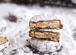 Puppy chow ritz cracker cookies on a bed of powdered sugar