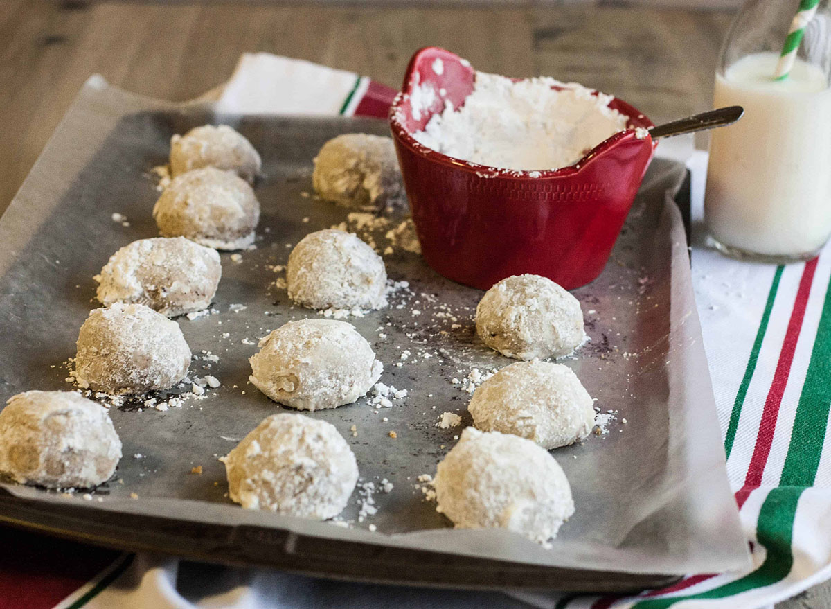 Toasted pecan cookies on a baking sheet with powdered sugar