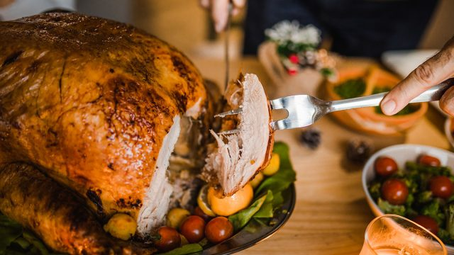 Close up ofman carving roasted Thanksgiving turkey.
