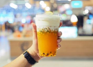 hand holding chinese iced tea with boba and cream cheese foam