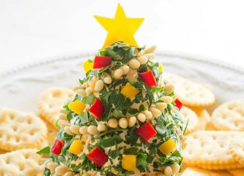 cheese shaped like christmas tree with chopped peppers and crackers