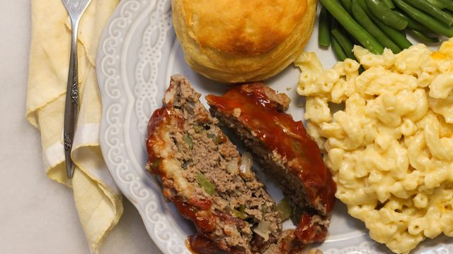 Slices of meatloaf on a plate with sides.
