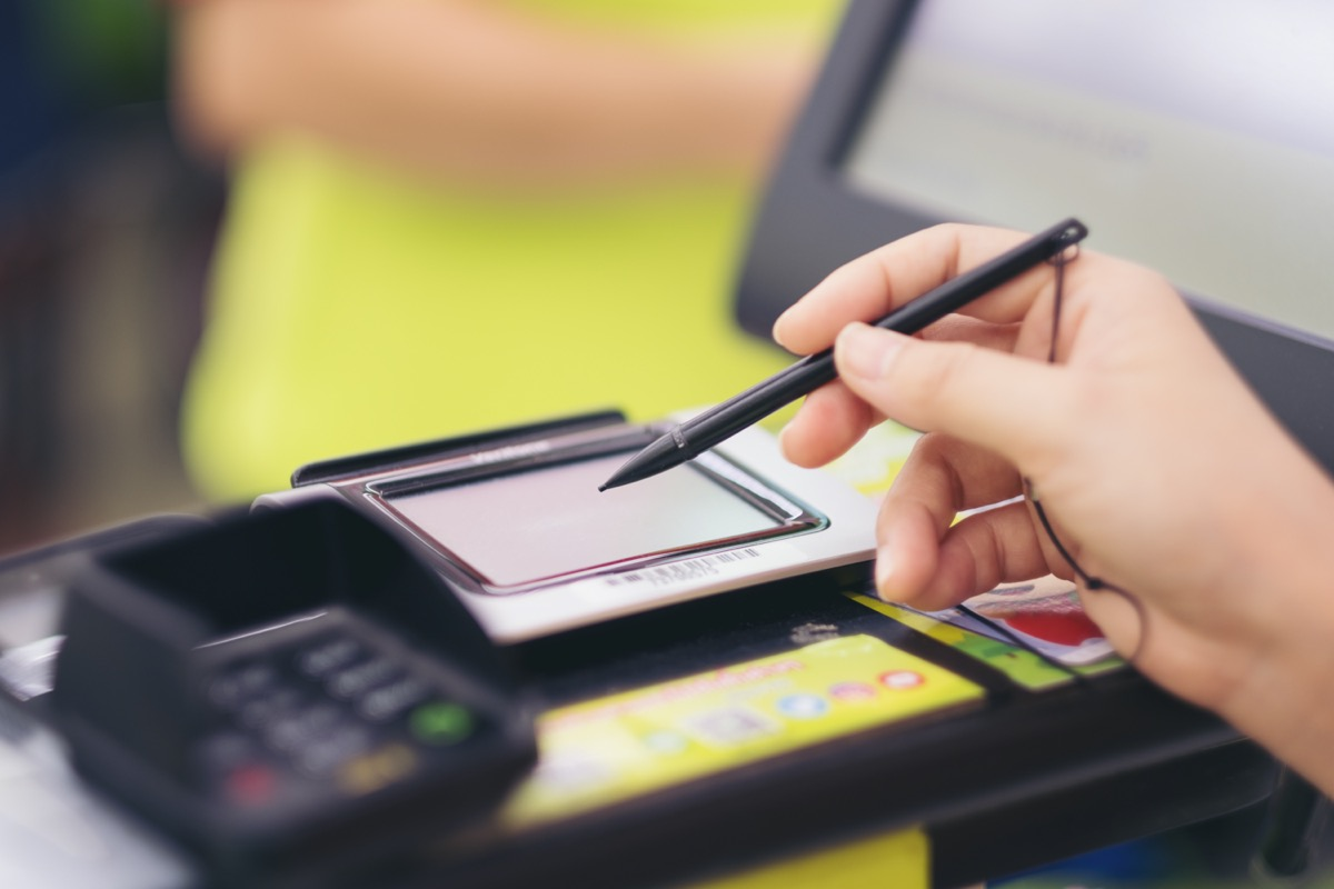 Close-up of consumer's women hand signing on a touch screen of credit card sale transaction receipt machine at supper market