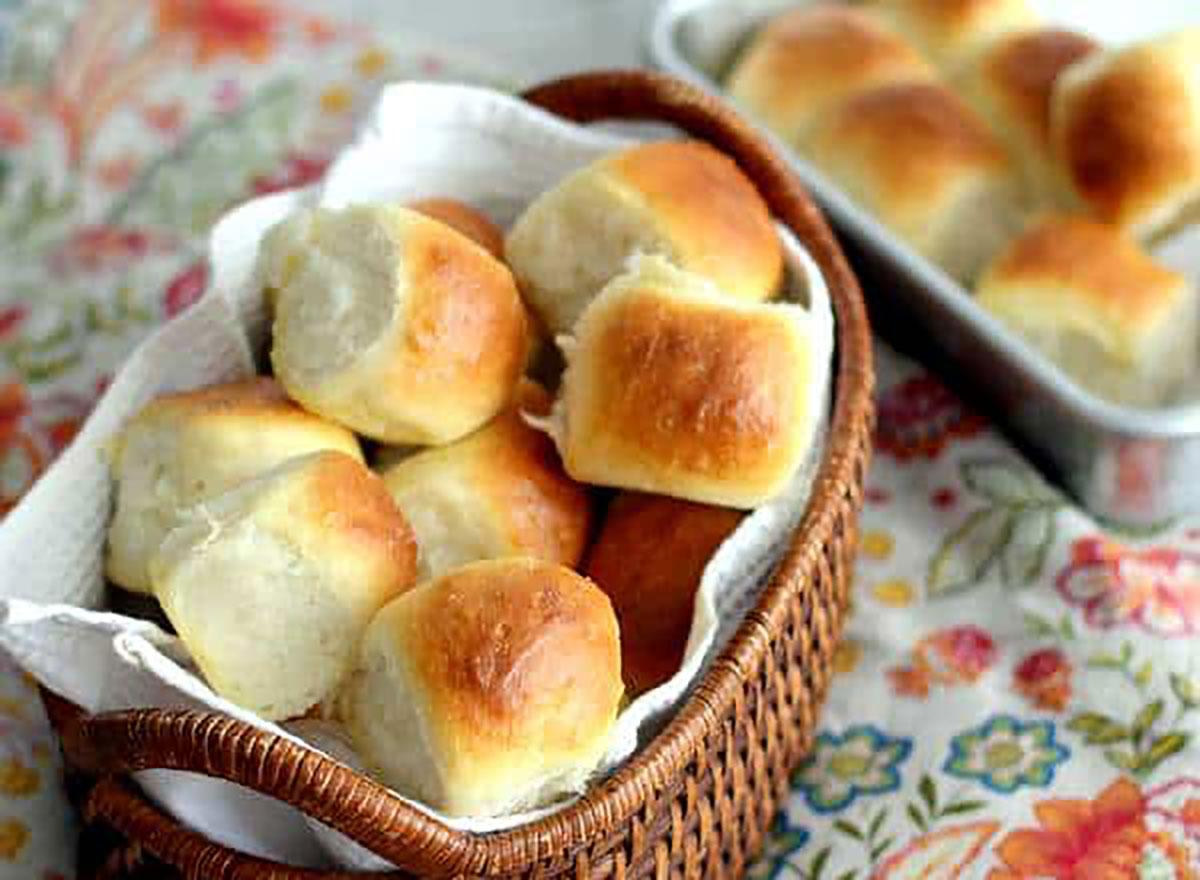 basket of dinner rolls on tablecloth
